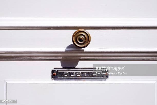 Close-Up Of Nameplate And Handle On Wooden Door During Sunny Day
