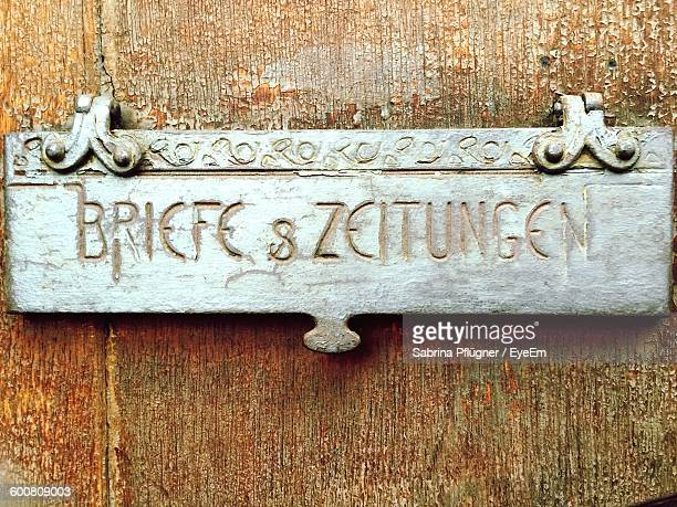 Close-Up Of Nameplate On Old Wooden Door