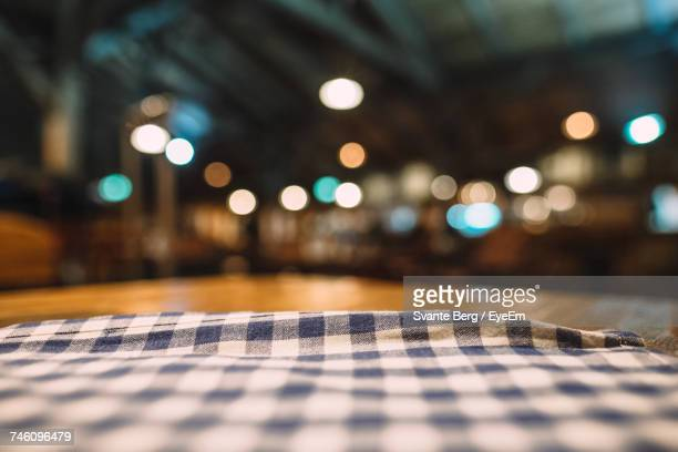 Close-Up Of Napkin On Table Against Illuminated Lights