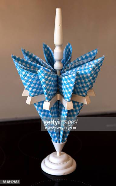 Close-Up Of Napkins Arranged On Holder At Table Against Wall
