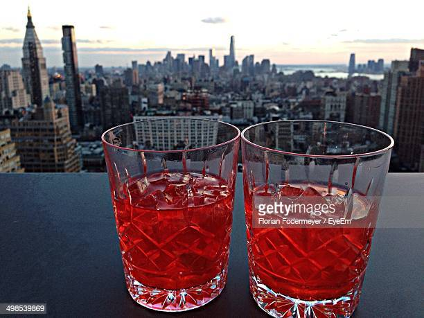 Close-up of Negroni cocktail with cityscape in background