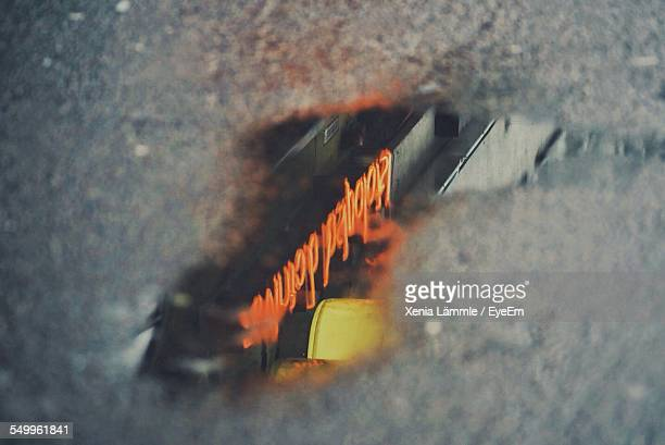 Close-Up Of Neon Signboard Reflecting In Puddle
