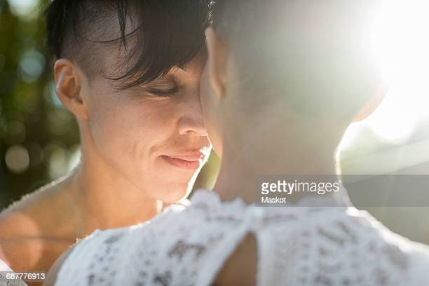 Close-up of newlywed lesbian couple embracing outdoors