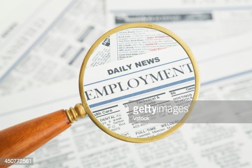 Close-up of newspaper page seen through magnifying glass