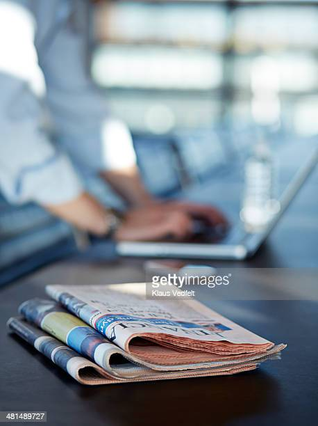 Close-up of newspapers & hands writing on laptop