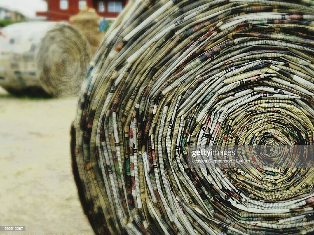 Close-Up Of Newspapers Rolled Up On Field : Stock Photo