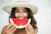[Note for inspector: Photo files for becoming exclusive contributor] Closeup portrait of smiling young beautiful woman looking aside, holding slice of watermelon and eating it. Front view.
