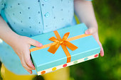 Close-up of nicely wrapped birthday gift being held by a child with no face visible. Party time concept