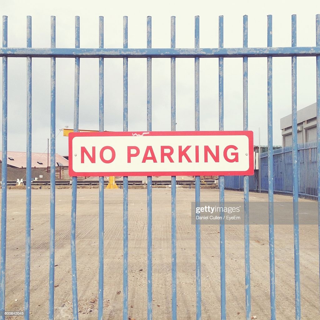 Close-Up Of No Parking Sign On Blue Metal Fence