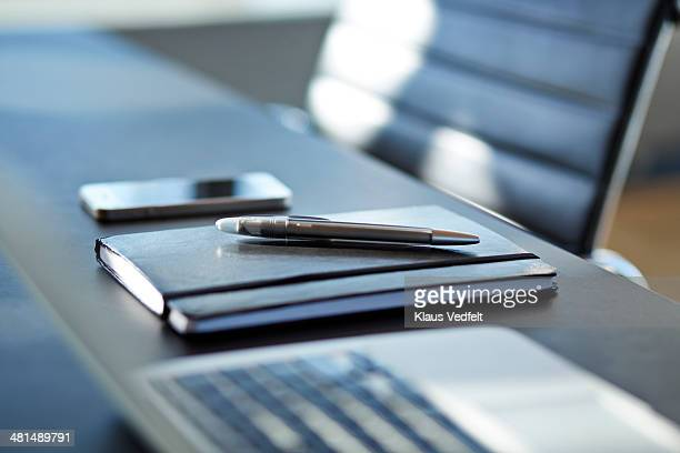 Close-up of notebook with pen on top,phone in back
