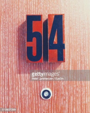 Close-up of number 54 and peephole on door