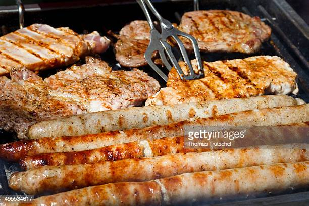 Closeup of Nuremberg Bratwursts and steaks crackling on a grill on March 31 2014 in Buecheloh Germany Meat on a BBQ