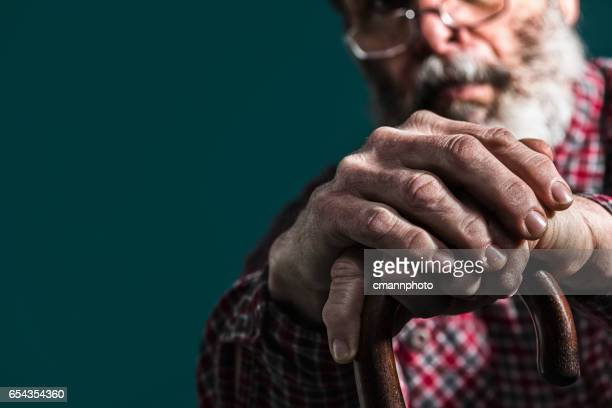 Close-up of old man's arthritic hands on cane