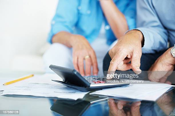 Closeup of old man's hand calculating bills at home