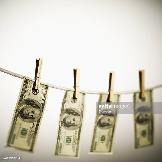 Close-up of one hundred dollar bills hanging on clothesline