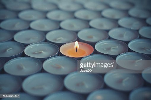 Close-up of one lit tea light surrounded by other tea lights