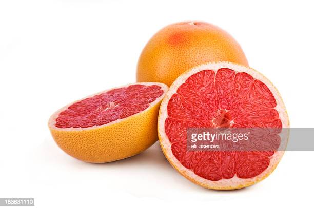 Close-up of one sliced and one full grapefruit