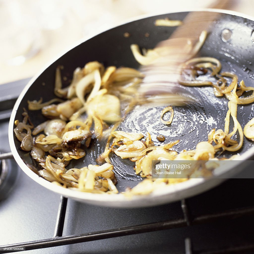 Close-up of onions being grilled in a pan.