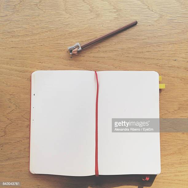 Close-Up Of Open Book With Pencil And Sharpener On Table