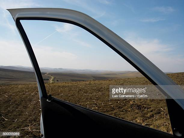 Close-up of open car door against landscape