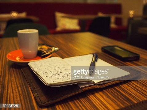 closeup of coffee cup on open book at table stock photo | getty images