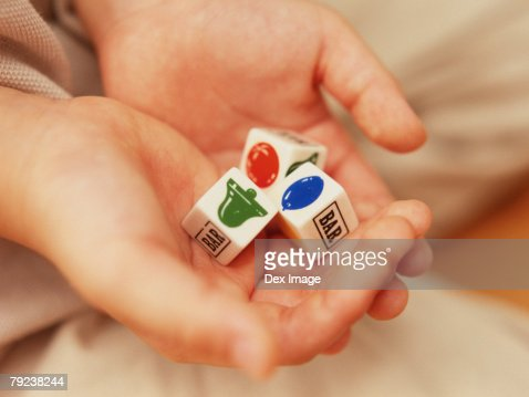 Close-up of opened hands holding dice : Stock Photo