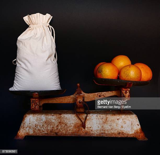 Close-Up Of Orange And Money Bag On Old Rusty Weight Scale Against Black Background