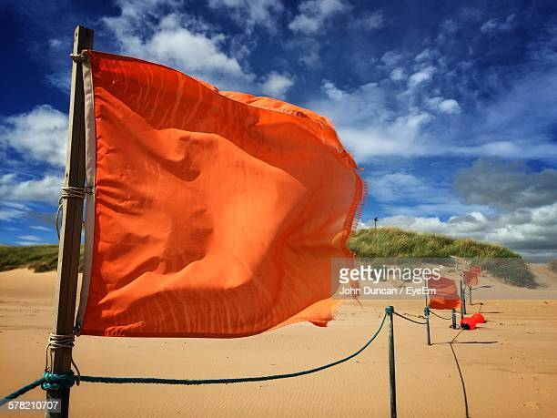 Close-Up Of Orange Flag Waving On Beach Against Sky