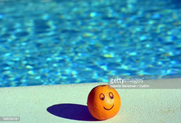 Close-Up Of Orange Fruit With Anthropomorphic Face On Swimming Pool
