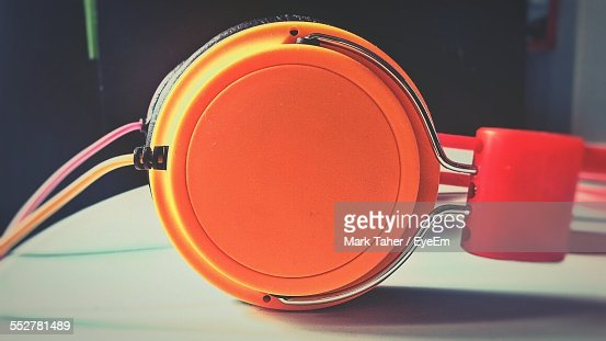 Close-Up Of Orange Headphones On Table At Home
