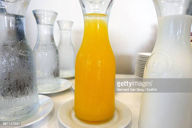 Close-Up Of Orange Juice Amidst Drinking Water And Milk In Bottles On Table