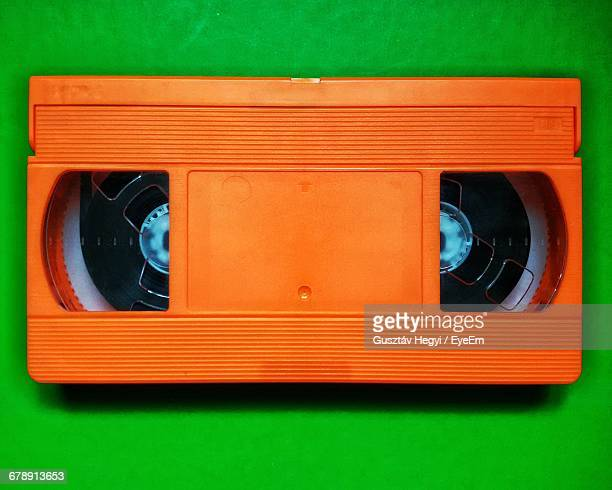 Close-Up Of Orange Videocassette On Green Table