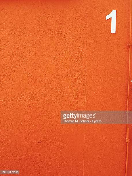 Close-Up Of Orange Wall With Number 1