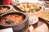 Photo of oriental pots with food at open food market can be used ofr any gourmet purposes, city lifestyle, open market and streed food