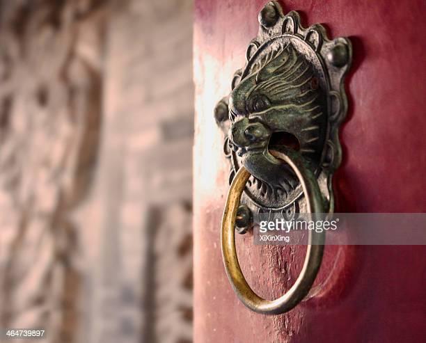 Close-up of ornate gold door knocker on red door
