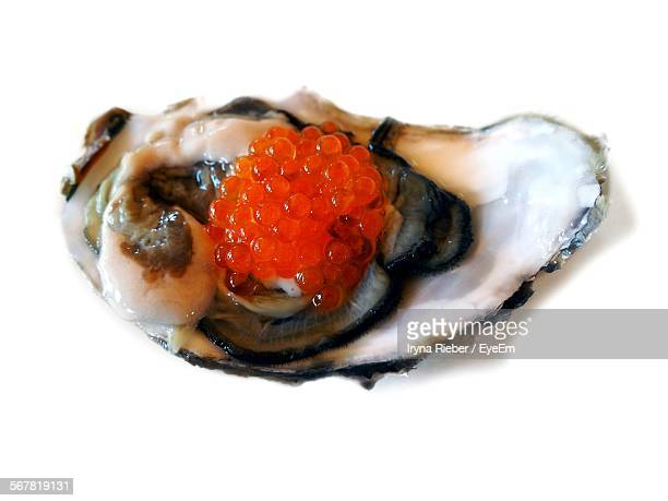 Close-Up Of Oyster And Red Caviar Against White Background