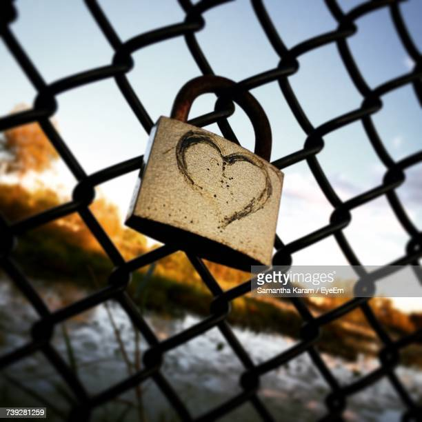 Close-Up Of Padlock On Chainlink Fence