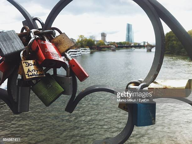 Close-Up Of Padlocks Hanging On Metal Fence By River
