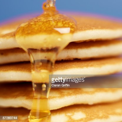 Close-up of pancakes stacked high with syrup being poured over them : Stock Photo