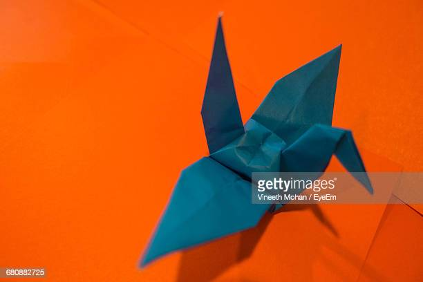 Close-Up Of Paper Bird Against Orange Background