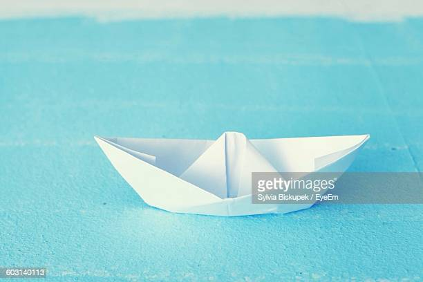 Close-Up Of Paper Boat On Blue Surface