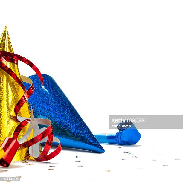 Close-up of party hats, whistle, confetti, streamer, isolated on white