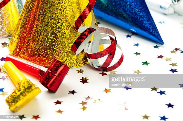 Close-up of party hats, whistles, streamers, confetti, isolated on white