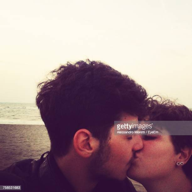 Close-Up Of Passionate Couple Kissing At Beach During Sunset