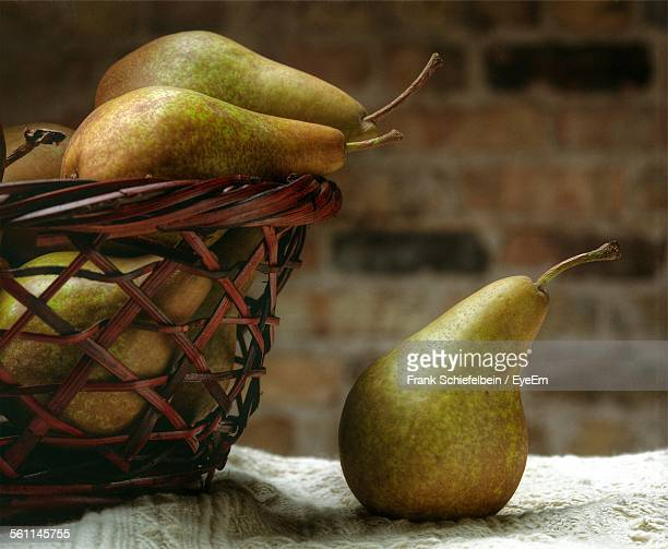 Close-Up Of Pear In Basket On Table Against Wall