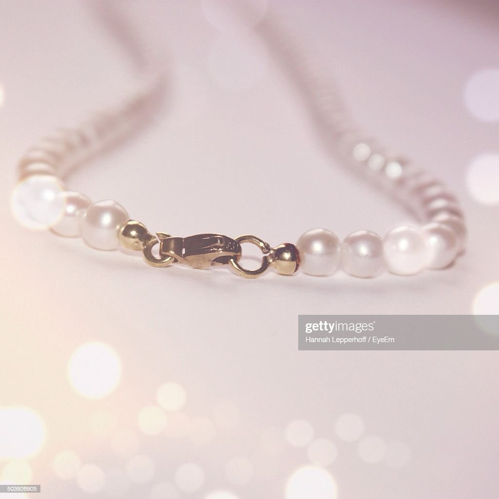 Close-up of pearl necklace hook on table