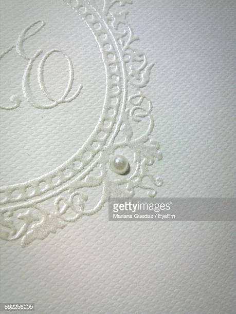Close-Up Of Pearl On White Wedding Invitation Card