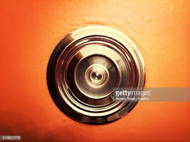 Close-up of peephole on orange door