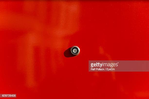 Close-Up Of Peephole On Red Door