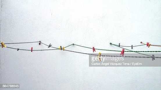 Wall Art Washing Line : Closeup of pegs on washing line against white wall stock